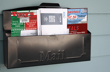photo of mailbox on a wall with a large postcard and other mail sticking out the top.